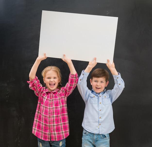 Dos niños pequeños que mantienen una hoja de papel en blanco sobre sus cabezas