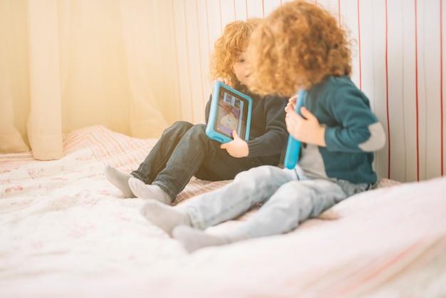Dos niños pequeños sentados en la cama jugando con tableta digital