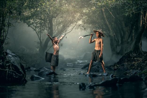 Dos niños pescando en arroyos