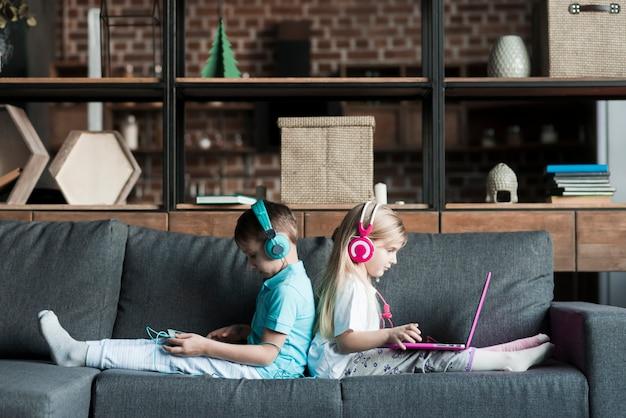 Dos niños en sofá con portátil Foto gratis