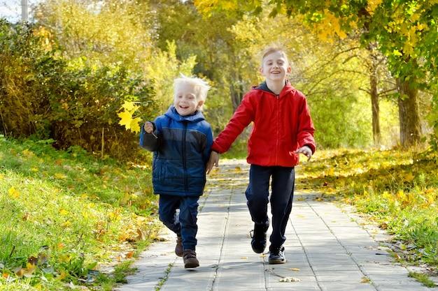 Dos niños sonrientes corren por el parque de otoño