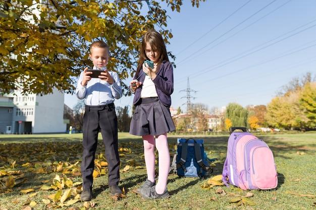 Dos niños con teléfonos móviles