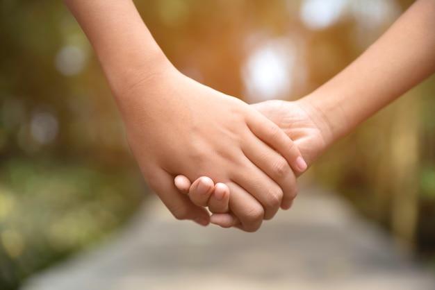 Dos niños tomados de la mano en el camino de madera