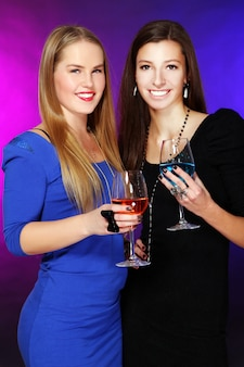 Dos novias alegres con coloridos cócteles