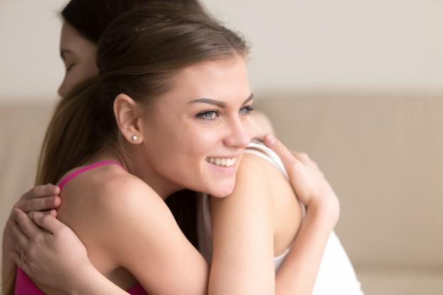 Dos novias jóvenes abrazándose, niña sonriendo alegremente