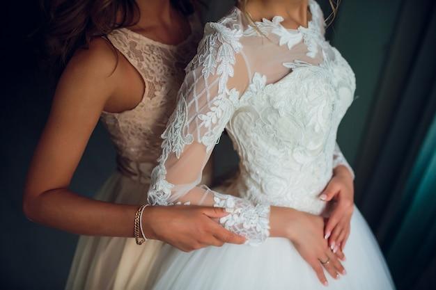 Dos novias susurran sobre algo y se ríen. hermosas chicas delicadas en vestidos de novia.