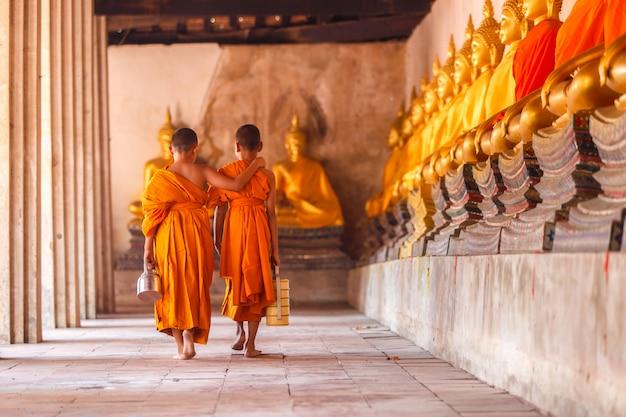Dos novicios caminan de regreso y hablan en el antiguo templo al atardecer, provincia de ayutthaya, tailandia.