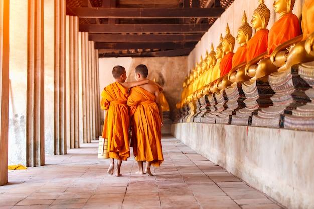Dos novicios caminando y hablando en el antiguo templo en la provincia de ayutthaya, tailandia