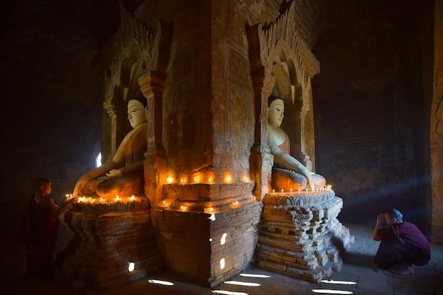 Dos novicios encienden velas y rezan en la pagoda de bagan en myanmar.
