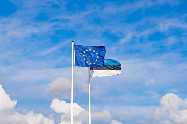 Dos ondeando banderas de la unión europea y estonia contra el cielo azul. el día de la independencia de estonia se celebra el 24 de febrero