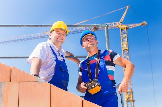 Dos orgullosos trabajadores del sitio de construcción o albañiles de pie en el proyecto de la casa dirigiendo la grúa con un control remoto