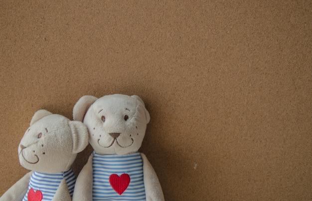 Dos oso de peluche con corazón sobre fondo de tablero de corcho