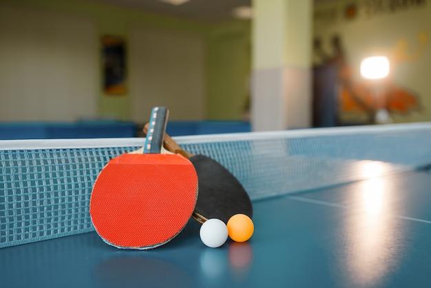 Dos paletas de ping pong en la mesa con red