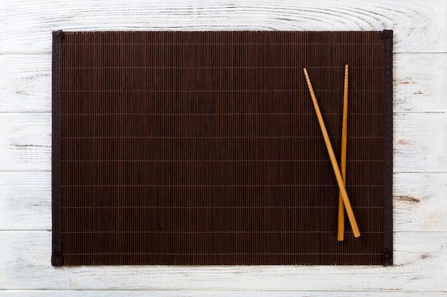 Dos palillos de sushi con estera de bambú vacía o placa de madera en madera blanca