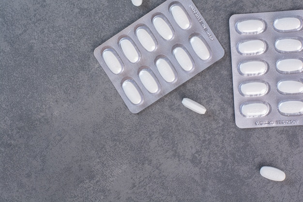 Dos paquetes de pastillas blancas sobre la mesa de mármol.