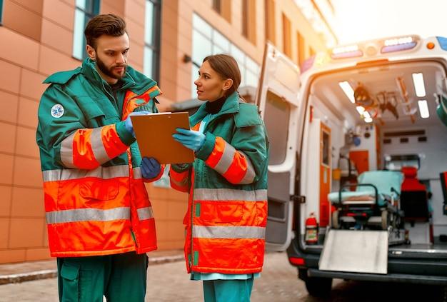Dos paramédicos uniformados discuten mientras están parados frente a una clínica y una ambulancia moderna.