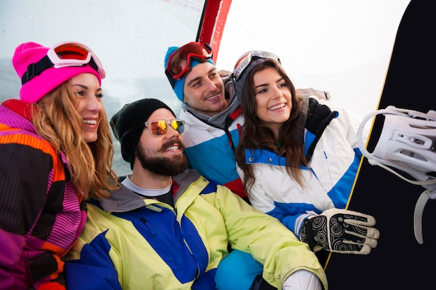 Dos parejas divirtiéndose y haciendo snowboard.