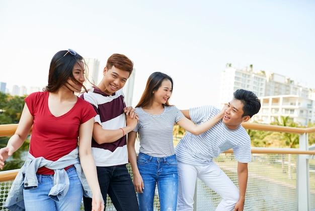 Dos parejas jóvenes divirtiéndose juntos al pasar tiempo al aire libre