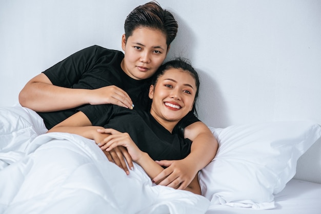 Dos parejas de mujeres abrazados juntos en la cama.