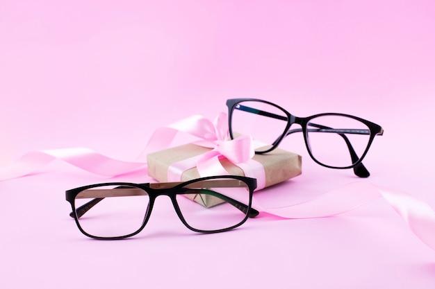 Dos pares de anteojos negros sobre superficie rosa