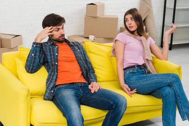 Dos pares jovenes trastornados que se sientan en el sofá amarillo en su nueva casa