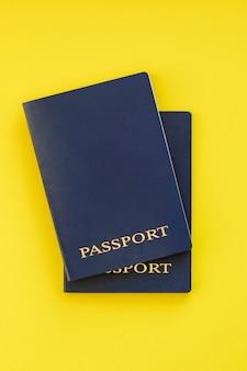 Dos pasaportes azules sobre un fondo amarillo