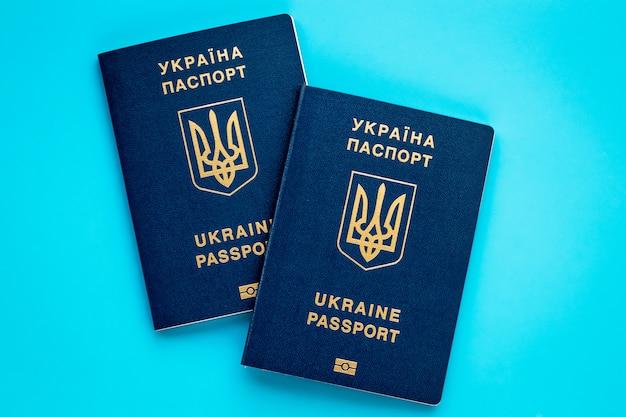 Dos pasaportes biométricos ucranianos sobre fondo azul. concepto de planificación de vacaciones. pasaporte internacional.