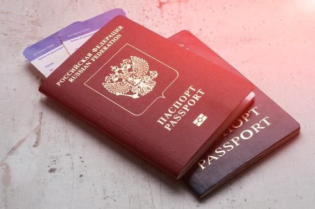Dos pasaportes de los viajeros ruso y bielorruso con tarjetas de embarque para el avión. t