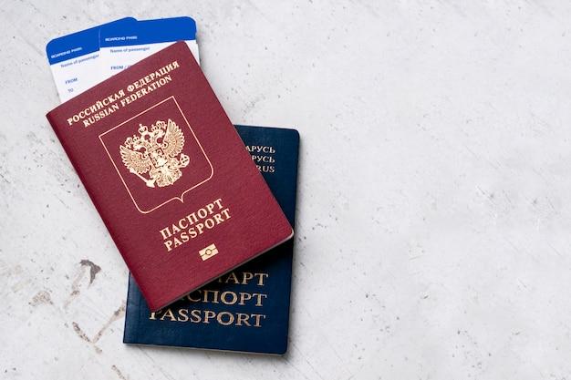 Dos pasaportes de los viajeros ruso y bielorruso con tarjetas de embarque para el avión.