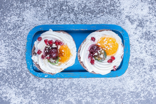 Dos pasteles cremosos con azúcar en polvo en una placa azul
