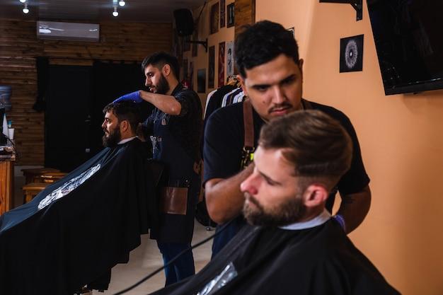 Dos peluqueros barbudos dando cortes de pelo a clientes masculinos en la barbería - barberos trabajando en su salón de hombres.