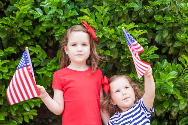 Dos pequeñas hermanas adorables que sostienen banderas americanas al aire libre en día hermoso de verano