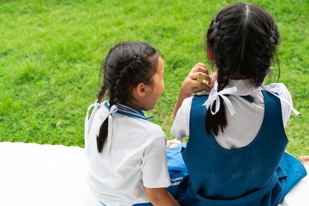 Dos pequeñas hermanas asiáticas de las muchachas que abrazan la publicación feliz en uniforme escolar, de nuevo a concepto de la escuela