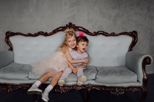 Dos pequeñas hermanas bastante jovenes elegantes que presentan en el estudio