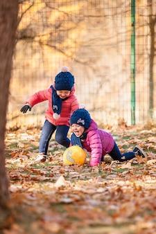 Las dos pequeñas niñas jugando en hojas de otoño