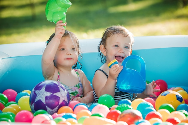 Las dos pequeñas niñas jugando con juguetes en la piscina inflable en el día soleado de verano