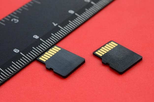 Dos pequeñas tarjetas de memoria micro sd se encuentran sobre un fondo rojo al lado de una regla negra.
