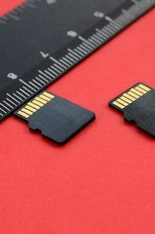 Dos pequeñas tarjetas de memoria micro sd se encuentran sobre un fondo rojo al lado de una regla negra