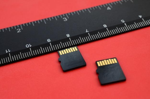Dos pequeñas tarjetas de memoria micro sd se encuentran sobre un fondo rojo