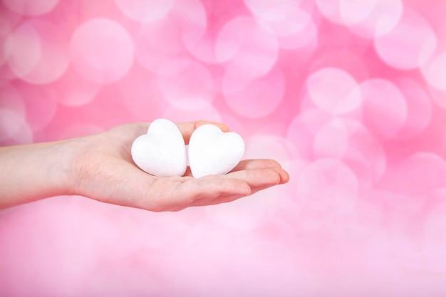 Dos pequeños corazones blancos en la mano sobre fondo rosa con bohe. saludo tarjeta de san valentín