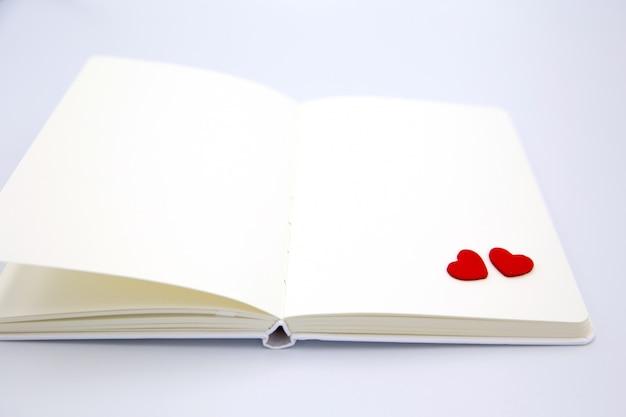 Dos pequeños corazones en la esquina del cuaderno en blanco