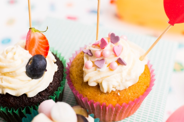 Dos pequeños cupcakes con bayas en mesa