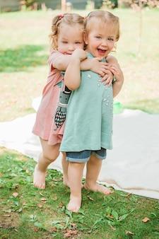 Los dos pequeños girsl bebé jugando contra la hierba verde en el parque