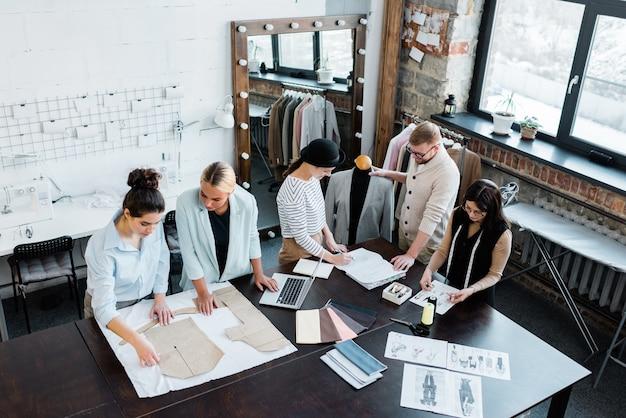 Dos pequeños grupos de diseñadores de moda profesionales que trabajan sobre nuevos bocetos y patrones de papel por mesa en el taller