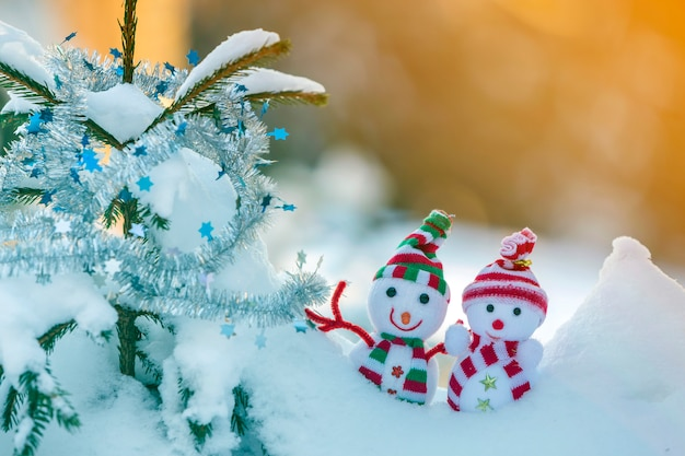 Dos pequeños juguetes divertidos bebé muñeco de nieve con sombreros de punto y bufandas en la nieve profunda al aire libre cerca de la rama de pino.