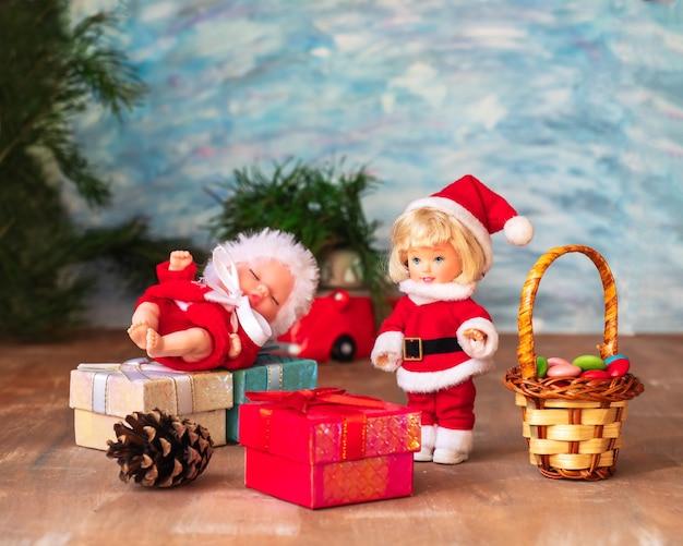 Dos pequeños santa junto a cajas con regalos un árbol de navidad sobre un fondo de madera