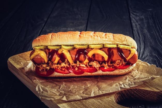 Dos perros calientes con primer plano de salsa de tomate, mostaza amarilla y cebolla sobre superficie de madera gris.