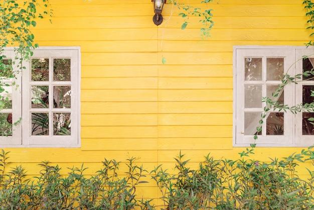 Dos persianas blancas en la pared de madera amarilla, la rama de un árbol verde sale del edificio