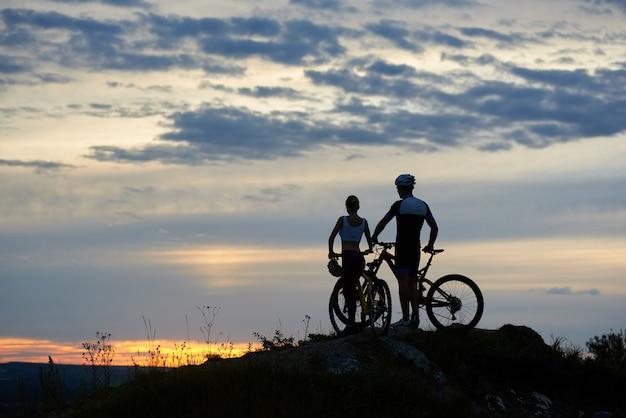 Dos personas con bicicletas de montaña se paran en la cima del acantilado al atardecer