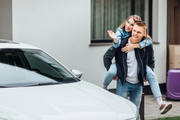 Dos personas casadas atractivas que compran un coche blanco nuevo y son felices.